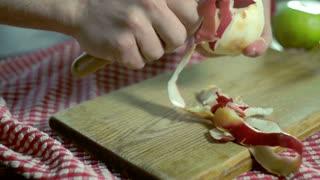 Peeled apple. Hands peeling fresh apple. Healthy food. Vegan breakfast. Peeling apples with special knife for fruit peeling. Vegetarian food