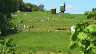 People resting on green meadow at spring park. Green trees and old windmill on background. People on recreation under blue sky and spring landscape with wooden mills. Recreation park