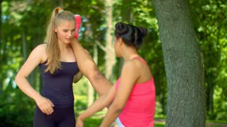 Personal trainer helping girl in leg stretching workout. Instructor helps to do stretching exercise. Two fitness woman doing yoga stretching exercise. Fitness workout and stretching outdoors