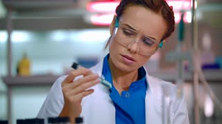 Pharmaceutical researcher in lab. Woman scientist mixing liquid in test tube. Lab technician conducting pharmaceutical research. Close up of pharmaceutical scientist working with liquid in flask