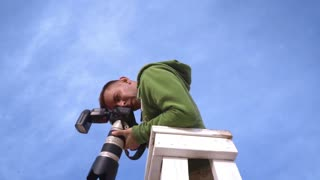 Photographer takes picture from watchtower. Photographer on sky background. Photographer with camera. Professional camera. Photographer shooting love couple from high point. Professional photographer