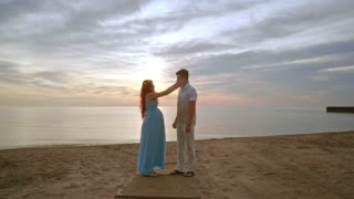 Pregnant couple on beach at sunrise. Man and woman on sea beach. Pregnant woman with husband on beach. Tenderness concept. Romantic couple beach. Happy couple on beach sunrise