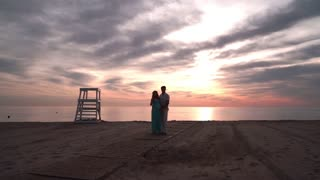 Pregnant couple talking at sunset. Love concept. Romantic couple on sea beach at sunset. Couple in love on sunset beach. Family on sea coast. Couple on sea beach. Love couple at sea beach at sunset