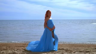 Pregnant model in blue dress flying on wind. Romantic photo session for pregnant family. Pregnant belly. Pregnant fashion. Pregnancy concept. Pregnant woman on beach sea. Pregnant girl
