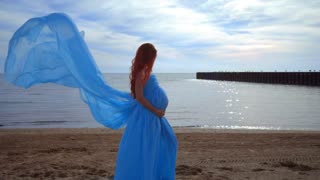 Pregnant woman in blue dress flying on wind. Pregnancy concept. Pregnant lady on beach. Pregnant fashion. Pregnant belly. Happy pregnant woman. Pregnant girl posing on beach. Woman pregnant