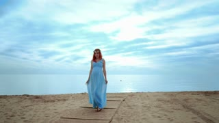 Pregnant woman walking on beach at morning. Redhead woman in blue dress walking on sea beach at sunrise. Pregnant lady on sea beach. Pregnancy concept. Woman pregnant. Pregnant beach