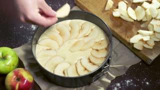 Preparing for baking apple pie. Cook puts apple slices in baking dish. Baking cake. Ingredients for baking apple cake. Sliced apples on cake batter in baking pan. Making apple pie. Sweet food