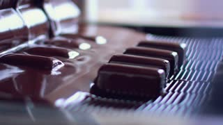 Production of chocolates. Candy poured by chocolate on production line. Food production line. Chocolate desserts on conveyor belt at chocolate factory. Food factory. Food processing plant. Chocolate factory. Manufacturing line at food factory