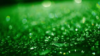 Rain drops on glass surface at night. Droplets on glass after rain. Closeup of shiny water drops on glass after rain. Green colored water droplets on glass. Water droplets. Abstract background