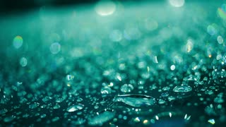 Rain drops on glass surface in aquamarine color. Macro of droplets on glass after rain. Closeup of shiny water drops on glass at night. Water droplets on glass in aquamarine color. Abstract background