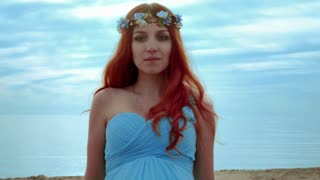 Red hair woman portrait on sea coast. Closeup of redhead woman in blue dress on blue sky background. Pregnant woman walking on sea beach. Close up of red hair girl. Redhead girl