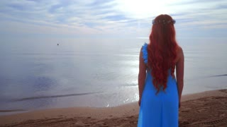 Redhead woman looking at sea. Rear view woman beach. Woman on sea beach. Woman relaxing on sea coast. Girl standing near ocean. Woman beach sunset. Loneliness concept. Dreaming woman. Woman sea sunset