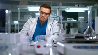 Researcher analyzing liquid in glass flask and writing data at research lab. Lab worker doing chemical research. Scientist working at chemical laboratory. Chemist doing experiment at laboratory