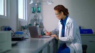 Researcher in lab. Young woman working in laboratory. Student writing research report. Serious clinician taking notes in chemical laboratory. Scientist working in modern laboratory. Female scientist