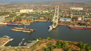 River port aerial view in small Asia town. Aerial view of industrial region of small city. Helicopter view of commercial cargo boat at river port. Industrial cranes unload commercial containers from ship