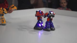 Robot fight on white ring. Toy robots fighting. Robot wars kids toys. Two transformer robots boxing. Robotic technology game. Battle robot game. Boxing robots