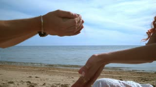 Sand pouring in human hands on beach. Relaxation concept. Closeup of male hand pours sand on female hands. Hands sand. Sand flowing through woman hands. on beach. Hand pours sand. Beach holiday
