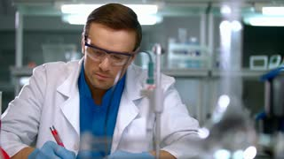 Scientist checking test tube with pink liquid. Scientist doing laboratory research. Laboratory researcher working with liquid in lab. Worker checking glass flask in chemical lab. Scientific experiment