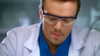 Scientist corrects glasses. Portrait of scientist focused on work. Scientist face close up. Laboratory worker in protective glasses. Young researcher in lab. Lab worker in medical gloves