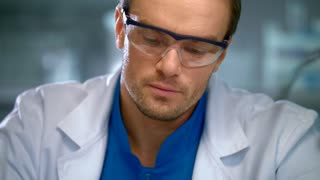 Scientist face. Portrait of researcher working in safety glasses. Laboratory worker face. Laboratory man focused on work. Concentrated lab worker working with chemical liquids in glass flask at lab