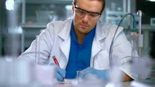 Scientist in lab doing medical research. Laboratory worker pour liquid from flask to measuring cup. Scientist laboratory working with chemical liquids. Chemist working at chemistry laboratory