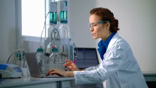 Scientist in lab. Female scientist check laboratory equipment. Scientist analyzing working process. Scientist working with equipment in modern lab. Scientific research in chemistry laboratory