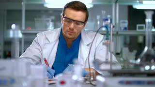 Scientist in lab. Scientist looking at chemical liquid in research laboratory. Scientist working in laboratory with chemical reagents. Lab man carrying out scientific research in lab. Scientist lab