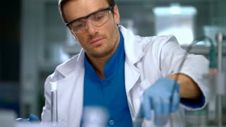 Scientist man carrying out scientific research in a lab. Young researcher working with liquid in chemical lab. Male scientist pouring liquid glass flask. Lab worker carrying out scientific research