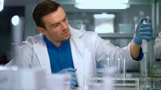 Scientist man using pipette in lab. Researcher with dropper working in laboratory. Scientist student working in lab. Lab worker using laboratory equipment. Laboratory scientist working with pipette