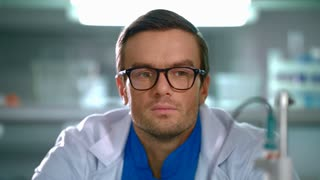 Scientist remove glasses from face. Scientist looking at glasses. Man holds glasses in hands. Portrait of lab man thinking in laboratory. Scientist in lab. Researcher thinking. Closeup lab worker