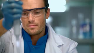 Scientist working in lab. Concentrated scientist face. Researcher using pipette in laboratory. Laboratory worker conducting chemical research in lab. Scientist in lab. Chemist focused on work