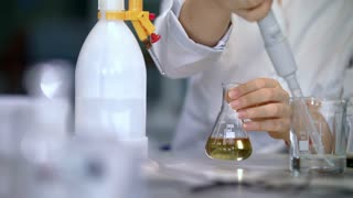 Scientist working with chemical reaction in chemistry lab. Chemical reaction in glass flask. Lab worker doing chemical experiment in laboratory. Researcher use pipette to drop liquid in glass flask