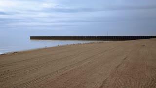 Sea beach with sea gulls and pier. Sea beach background. Seagulls on beach. POV walking on sea beach at sunrise. Sunrise sea. Blue sky. Calm sea surface. Sea beach with pier