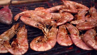 Seafood grilled on barbecue. Panorama of shrimps, fish and other sea food on barbecue grill. Chef grilling seafood on bbq. Closeup of grilled shrimps and sea fish. Seafood delicacies cooked on grill