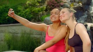 Selfie friends outdoors. Joyful girls having fun in park taking selfie. Multiracial friends take photo with phone. Two happy girlfriends taking selfie photo with smartphone camera. Women taking selfie