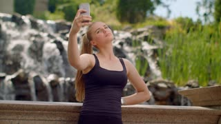 Selfie girl. Caucasian girl taking selfie near waterfall. Selfie woman. Woman selfie. Young woman taking self photo in park. Different expressions on woman face. Sport woman making self portrait