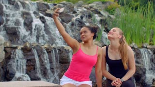 Selfie women. Two young women taking selfie near waterfall. Women selfie. Selfie photo. Selfie girls. Funny women taking photo with phone in park. Cheerful girls posing for photo outdoor