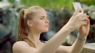 Sensual woman taking selfie in park. Close up of sexy girl taking photo with phone. Selfie woman. Blonde girl with sensual face expression taking selfie outside. Young woman smiling. Girl selfie