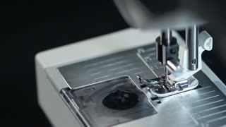 Sewing needle in slow motion. Top view of working sewing machine in slow motion. Manufacturing equipment. Process of working of the electric sewing machine.