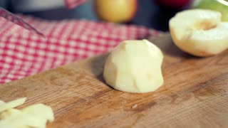 Slicing apple. Cutting apple. Cook cut apple at wooden plank in kitchen. Slicing peeled apple. Apple slice. A knife cutting apple in slices. Healthy food. Vegetarian food