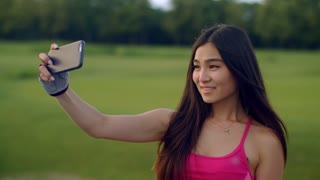 Smile girl taking selfie outdoors. Close up of sporty woman taking selfie photo on smartphone in park. Asian girl posing for selfie with phone. Happy girl posing for selfie portrait. Fit girl selfi