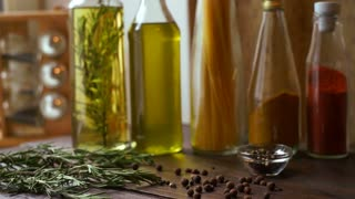 Spices and herbs on kitchen table. Closeup of cooking ingredients. Pepper spice scattered on wooden table. Rosemary herb. Peppercorns in glass bowl. Olive oil bottle. Cooking oil in glass bottle