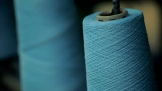 Spininng spool of thread. Cotton thread spool. Cotton yarn on bobbine at textile factory