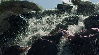 Splashes of water in slow motion. Close up of waterfall. Mountain waterfall. Water splashing in sunlight. Water splash. Falling water in slow motion. Closeup of water rushing over stones