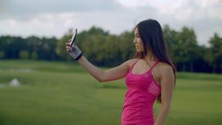 Sport woman selfie in park. Beautiful woman selfi with phone outdoor. Asian girl taking selfie photo on phone. Fitness woman posing for selfie portrait. Attractive girl selfie phone