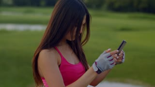 Sport woman using phone at park. Fit girl reading news on phone. Young woman using phone outdoor. Woman phone. Fitness woman using smartphone on green meadow. Asian girl reading sms on iphone