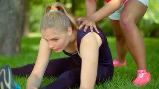 Stretching exercises outdoor. Close up of caucasian woman expressing pain while stretching in park. Mulatto girl help her friend to warm up muscles before fitness training outside