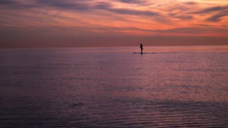 Sunset at sea. Man on surfboard at sunset. Sea sunset. Sunset landscape. Red color of sunset sky. Calm water at sunset sea. Sunset water. Sunset sea. Sunset clouds over water
