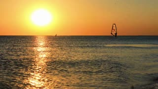 Sea sunset time lapse. Sun setting behind sea horizon. Golden sunlight reflection at sunset. Extreme sports at sunset timelapse. Surf. Kite. Jet. Sea sunrise. Sun shine reflection on water surface