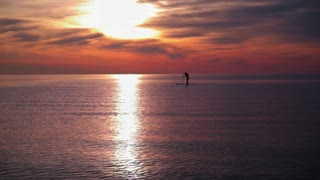 Sunset sea. Man rowing on surfboard at sunset. Sea sunset with calm water. Tranquil water of sunset sea. Calm sea waves at sea sunset. Surfing at sunset sea. Sun reflection at sea